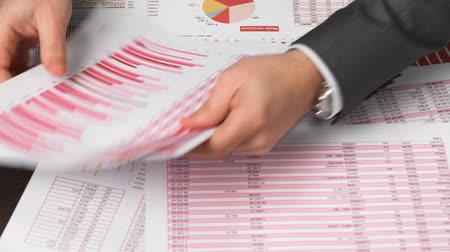 táblázatkezelő : Businessman accountant using calculator for calculating finance on desk office. Business financial accounting concept. Red reports and graphs. Office employee examines schedules and reports. Stock mozgókép