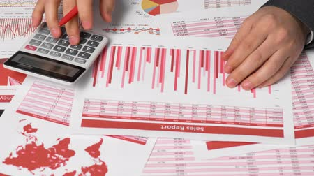 ksiegowosc : Businessman accountant using calculator for calculating finance on desk office. Business financial accounting concept. Red reports and graphs. Office employee examines schedules and reports. Wideo