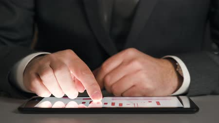 předpovídání : Businessman working on a tablet, analyzes the graphs and tables, hands closeup. Dostupné videozáznamy