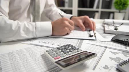 planilha : Businessman working at office and calculating finance, reads and writes reports. Business financial accounting concept.