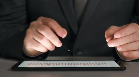 スイート : Businessman working on a tablet, analyzes the graphs and tables, hands closeup. 動画素材