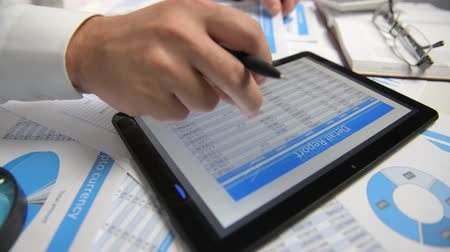 táblázatkezelő : Businessman working with tablet pc, calculating, reading and writing reports. Office employee, table closeup. Business financial accounting concept. Stock mozgókép