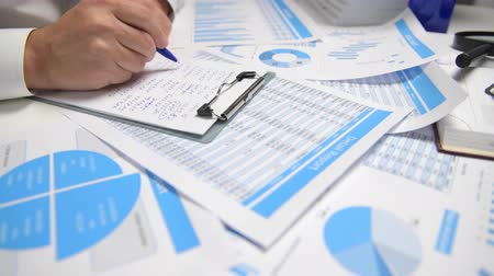 ksiegowosc : Businessman working and calculating, reads and writes reports. Office employee, table closeup. Business financial accounting concept.
