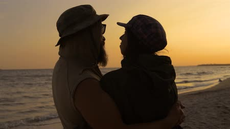 bigode : Young romantic travelers looking to the beach sky, enjoying sunset at the sea - love, summer and travel concept. Stock Footage