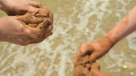 moldagem : Closeup of hands making clay on a sea beach, sand and wave as background, summer and travel concept.