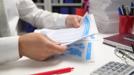 escrever : Businessman working and calculating, reads and writes reports. Office employee, table closeup. Business financial accounting concept.