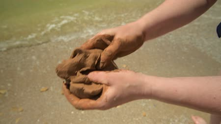 amarrotar : Closeup of hands making clay on a sea beach, sand and wave as background, summer and travel concept.