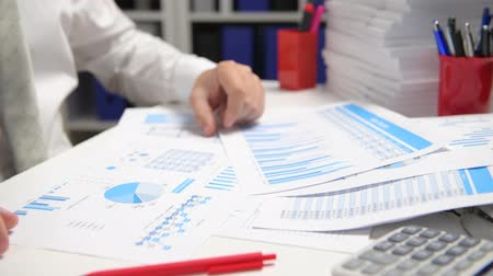 księgowa : Businessman working and calculating, reads and writes reports. Office employee, table closeup. Business financial accounting concept.