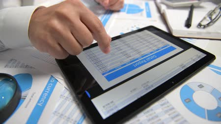 táblázatkezelő : Businessman working and calculating, reads and writes reports. Using tablet pc. Office employee, table closeup. Business financial accounting concept. Stock mozgókép
