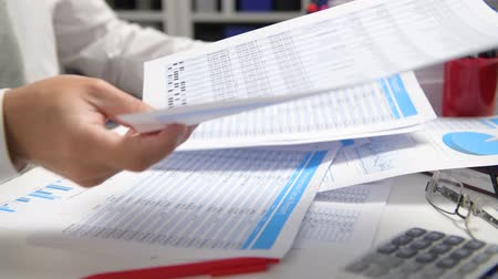 táblázatkezelő : Businessman working and calculating, reads and writes reports. Office employee, table closeup. Business financial accounting concept.