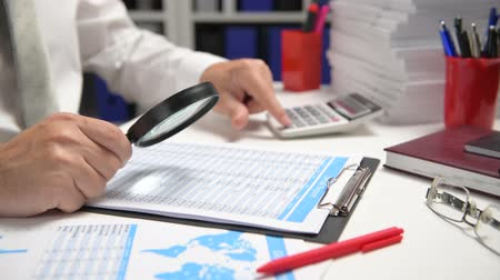 planilha : Businessman working and calculating, reads and writes reports. Office employee, table closeup. Business financial accounting concept.