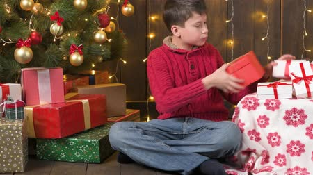 Boy sitting indoor near decorated xmas tree with lights and getting gifts - Merry Christmas and Happy Holidays!