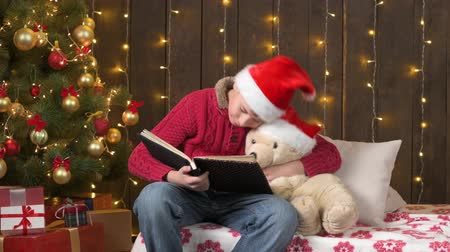 Santa helper boy reading book to bear toy, sitting indoor near decorated xmas tree with lights - Merry Christmas and Happy Holidays! Стоковые видеозаписи