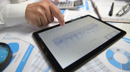 planilha : Businessman working and calculating, reads and writes reports. Using tablet pc. Office employee, table closeup. Business financial accounting concept. Vídeos