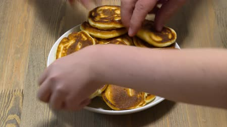 Quickly grabbing a delicious pancakes from the plate, a big hungry family and a lot of hands Стоковые видеозаписи