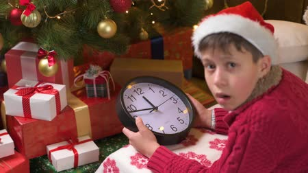 Teen boy waiting for Santa and watching the clock, lying indoor near decorated xmas tree with lights, dressed as Santa helper - Merry Christmas and Happy Holidays! Стоковые видеозаписи