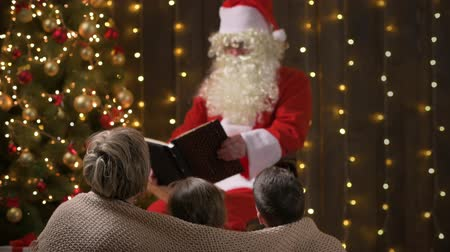 Santa reading book for family. Mother and children sitting indoor near decorated xmas tree with lights and listen - Merry Christmas and Happy Holidays!