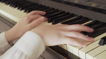 zongora : closeup of a young girl hands playing old piano