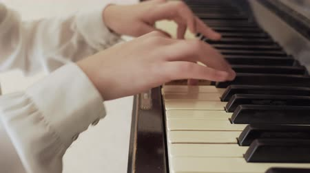closeup of a young girl hands playing old piano