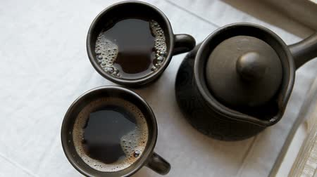 Two black coffee cups and clay ibrik on the wooden salver
