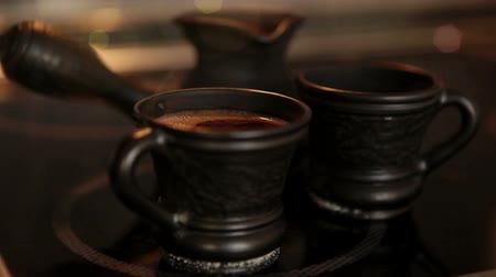 Clay coffee set Cezve and two cups with steaming coffe 影像素材