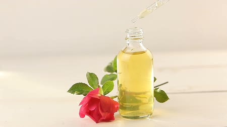 rose extract : Essence of rose on White background in a beautiful glass bottle Stock Footage