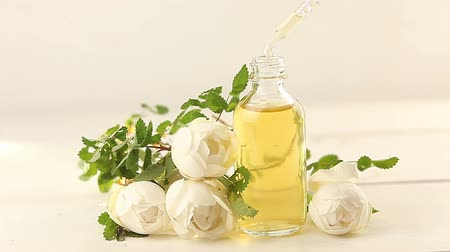 aromaterapia : Essence of flowers on white background in beautiful glass jar
