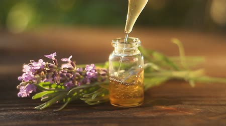 medicina alternativa : Aceite esencial de lavanda en hermosa botella en mesa Archivo de Video