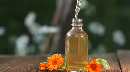 marigolds : Essence of flowers on table in a beautiful glass bottle