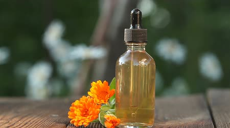 calendula blossoms : Essence of flowers on table in a beautiful glass bottle