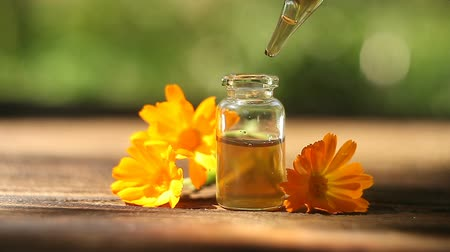 alternativní medicína : Essence of flowers on a table in a beautiful glass jar