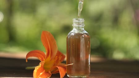aromaterapia : Essence of flowers on a table in a beautiful glass jar