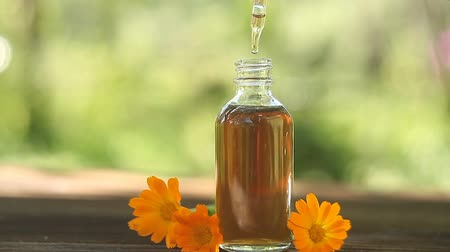 calendula blossoms : Essence of flowers on a table in a beautiful glass jar