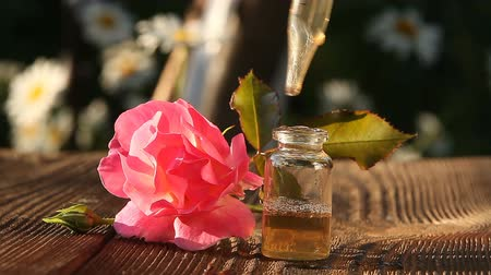rose extract : Essence of rose on table in a beautiful glass bottle Stock Footage