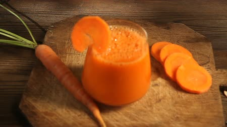 Carrot juice in glass on table Стоковые видеозаписи