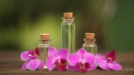 Essence of orchid flowers on a table in a beautiful glass jar