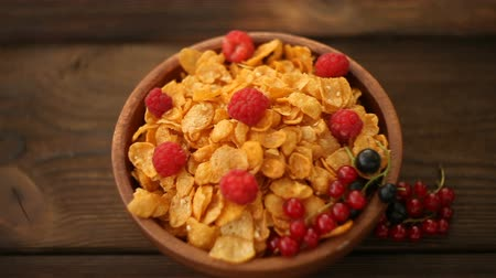 Breakfast of cornflakes with berries in wooden bowl Stok Video