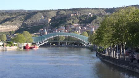 cura : View of the River Kura, a glass bridge of the world, the cable car and Narikala Fortress. The movement cars on the road. Tbilisi