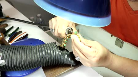 The goldsmith is repairing the luxury gold bracelet