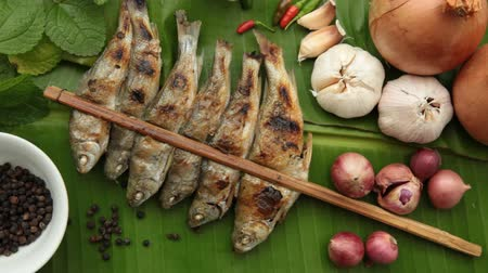 Grilled Fish and Onion, Garlic, Chilli, Pepper, Kaffir Lime leaves on Banana leaves