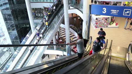 People riding on escalators in a Terminal shopping mall at Asoke Montri intersection , Sukhumvit road, Bangkok, Thailand, October 13, 2018