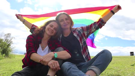 haklar : Two young women are sitting on a background of the rainbow flag. The sun is shining brightly, LGBT rights, lesbian family. Stok Video