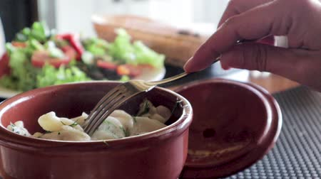 meat pockets : Dumplings in a clay pot. Hot food with steam, salad in the background.