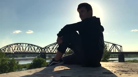 destino : Asian teenager sitting in the street in the background of the bridge and watching away from the camera. Slow-motion, bottom view.