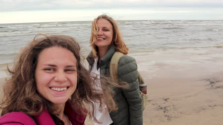 lesbian couple : Two young women walk along the beach and taking selfie on the background of the autumn sea.