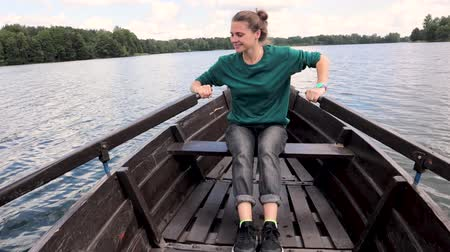kürek çekme : A young beautiful woman is sailing on a boat on the lake. A strong woman paddles with oars. Stok Video