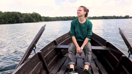 A young beautiful woman is sitting on a boat on the lake looking away from the camera.