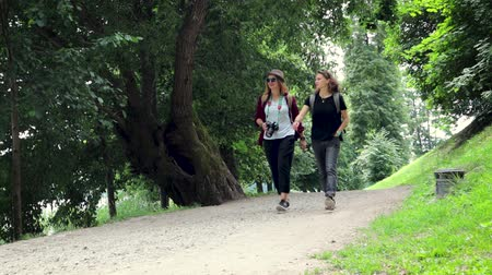 Two women tourists with backpacks are walking in the park.