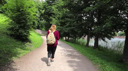 Young woman with a backpack is walking in the park. Walking away from the camera. Wideo
