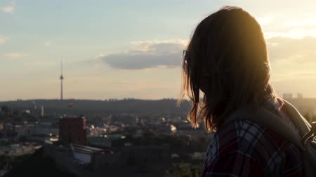 A young woman stands against the backdrop of the setting sun and looks at the city view.